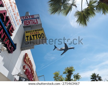 LOS ANGELES - April 29, 2015: Airplane plane flying over LA, framed inside signs and palm trees. - stock photo