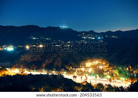 Los Angeles at night with Hollywood sign and highway - stock photo