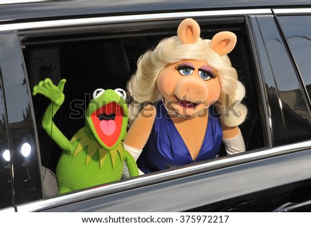 "LOS ANGELES, CA - MARCH 11, 2014: Muppets' characters Kermit the Frog & Miss Piggy at the world premiere of their movie Disney's ""Muppets Most Wanted"" at the El Capitan Theatre, Hollywood.  - stock photo"