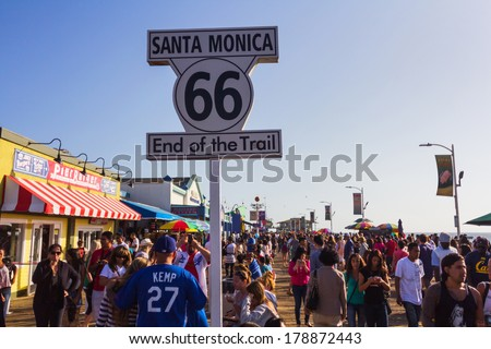 LOS ANGELES, CA -  MAY 27, 2013: People walking by Santa Monica end of famous Route 66 in Santa Monica Pier - stock photo