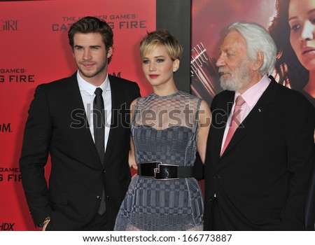 """LOS ANGELES, CA - NOVEMBER 18, 2013: Jennifer Lawrence, Liam Hemsworth (left) & Donald Sutherland at the US premiere of their movie """"The Hunger Games: Catching Fire"""" at the Nokia Theatre LA Live.  - stock photo"""