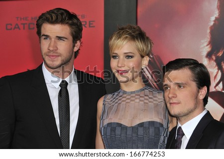 "LOS ANGELES, CA - NOVEMBER 18, 2013: Jennifer Lawrence with Liam Hemsworth (left) & Josh Hutcherson at the US premiere of their movie ""The Hunger Games: Catching Fire"" at the Nokia Theatre LA Live.  - stock photo"