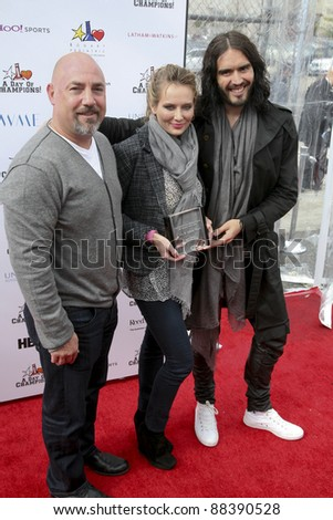 LOS ANGELES, CA - NOVEMBER 06: Russell Brand, Adam & Trina Venit arrive at Day Of Champions Benefiting the Bogart Pediatric Cancer Research Program at Sports Museum of Los Angeles on November 6, 2011. - stock photo