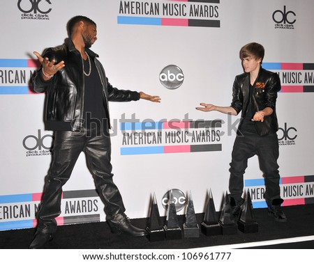 LOS ANGELES, CA - NOVEMBER 21, 2010: Usher & Justin Bieber (right) at the 2010 American Music Awards at the Nokia Theatre L.A. Live. - stock photo