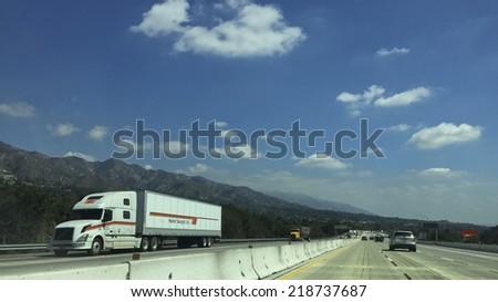 LOS ANGELES, CA - SEPTEMBER 19, 2014: Major highway traffic splitting Sunland-Tujunga near San Gabriel Mountains, highway I-210, Los Angeles suburb, California - stock photo