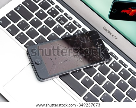Los Angeles, CA, USA - December 07, 2015: Broken Apple iPhone with cracked screen on Apple MacBook Air laptop - stock photo