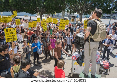 Los Angeles, CA, USA - May 02, 2015: Protestant talking to others during march against the death of Freddie Gray, a man of Baltimore who was seriously injured in police custody. - stock photo