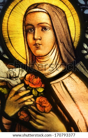 LOS ANGELES, CA, USA - NOVEMBER 27, 2013: Illustrative photo of a beautiful vibrant stained glass depicting nun holding crucifix and roses. - stock photo