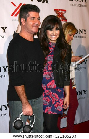 LOS ANGELES - DEC 6:  Simon Cowell, Demi Lovato arrives to the X Factor 2012 Final Four Party at Rodeo Drive on December 6, 2012 in Beverly Hills, CA - stock photo