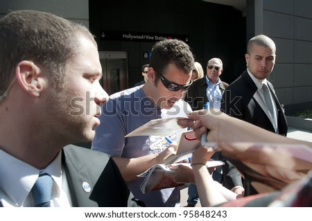 LOS ANGELES - FEBRUARY 22: Actor-comedian Adam Sandler signs autographs for fans at the Jennifer Aniston Hollywood Walk of Fame Star Ceremony at Hollywood Blvd  on February 22, 2012 in Los Angeles, CA - stock photo
