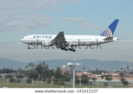 LOS ANGELES - JAN 15: A United Airlines 777 on approach to LAX on January 15, 2012 in Los Angeles.  The Boeing 777 is the largest twin engine jet in operation. - stock photo