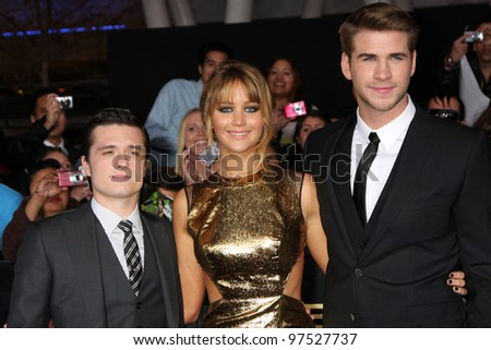 "LOS ANGELES - MAR 12:  Josh Hutcherson; Jennifer Lawrence; Liam Hemsworth arrives at the ""Hunger Games"" Premiere at the Nokia Theater at LA Live on March 12, 2012 in Los Angeles, CA - stock photo"