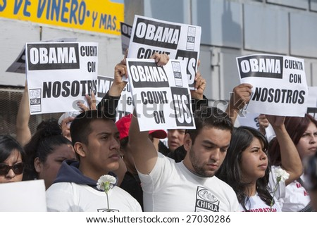 LOS ANGELES - MARCH 19: A crowd of CHIRLA demonstrators hold up signs of support for President Barack Obama on his visit to Los Angeles on March 19th, 2009. - stock photo