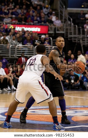 LOS ANGELES - MARCH 12: Washington Huskies G Isaiah Thomas #2 & Arizona Wildcats G Lamont Jones #12 during the NCAA Pac-10 Tournament basketball championship game on March 12 2011 at Staples Center in Los Angeles, CA. - stock photo