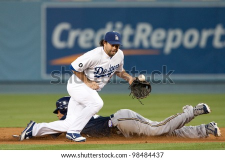 LOS ANGELES - MAY 16: Milwaukee Brewers CF Carlos Gomez #27 steals second past Los Angeles Dodgers 2B Aaron Miles #6 during the MLB game on May 16 2011 at Dodger Stadium in Los Angeles. - stock photo