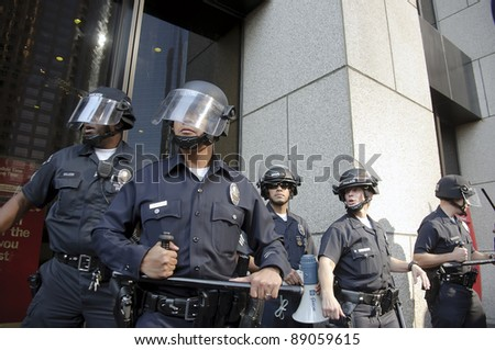 LOS ANGELES - NOVEMBER 17: Riot police stand guard outside a building of Bank of America during a Occupy LA rally on November 17, 2011 in Los Angeles, CA. - stock photo