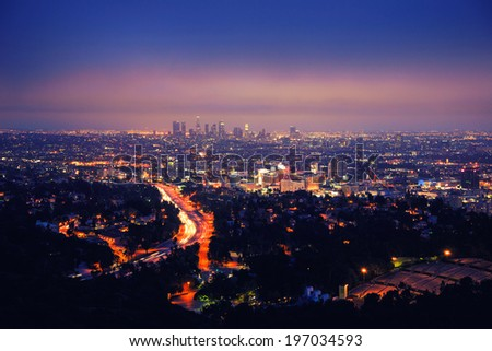 Los Angeles skyline at night, view from Hollywood Hills towards 101 freeway and downtown. - stock photo