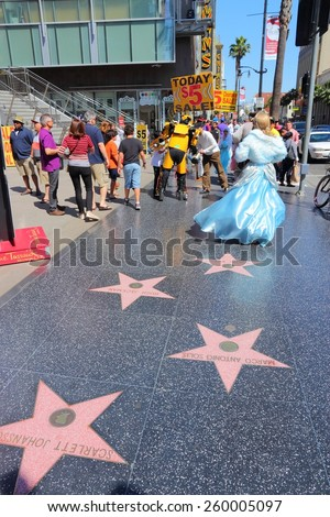 LOS ANGELES, USA - APRIL 5, 2014: People visit famous Walk of Fame in Hollywood. Hollywood Walk of Fame features more than 2,500 stars with inscribed celebrity names. - stock photo