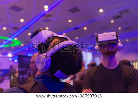 Los Angeles, USA - January 23, 2016: Men tries virtual reality Samsung Gear VR headset during VRLA Expo Winter, virtual reality exposition, at the Los Angeles Convention Center. - stock photo