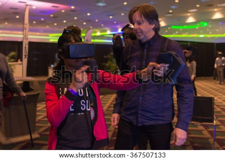 Los Angeles, USA - January 23, 2016: Woman tries virtual reality Samsung Gear VR headset during VRLA Expo Winter, virtual reality exposition, at the Los Angeles Convention Center. - stock photo