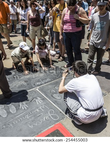 LOS ANGELES, USA - JULY 5, 2008: people admire the hand and Footprints of Harry Potter at the walk of fame in Los Angeles, USA. There are more than 200 hand and footprints at Chinese Theater. - stock photo