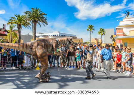 LOS ANGELES, USA - SEP 27, 2015: Unidentified girl tried to control a velociraptor in Jurassic Park area in the Universal Studios Hollywood Park. Jurassic Park is a 1993 adventure film  by Spielberg - stock photo