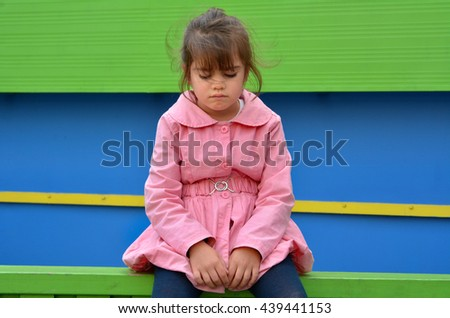 Lost child (girl age 6) lost in a city street cries on a fence. - stock photo