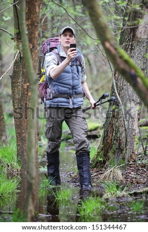 lost hiker in forest with mobile satellite navigation device - geo-caching  - stock photo