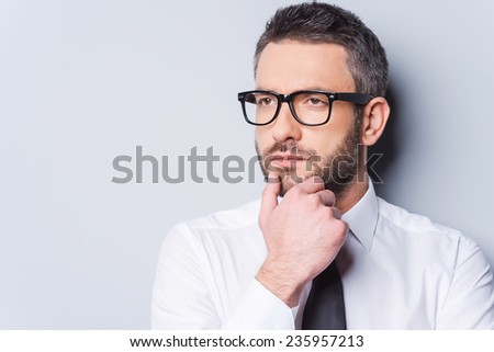 Lost in business thoughts. Portrait of thoughtful mature man in shirt and tie holding hand on chin and looking away while standing against grey background - stock photo