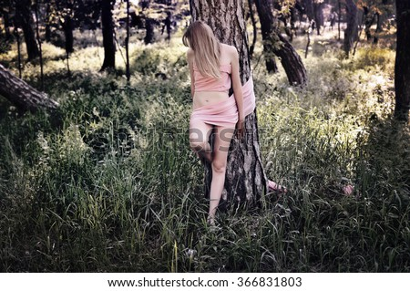 Lost in the forest. Naked woman tied with ribbon to a tree  - stock photo