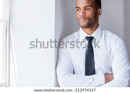 Lost in thoughts. Handsome young African man in shirt and tie looking through the window and keeping arms crossed while leaning at the wall - stock photo