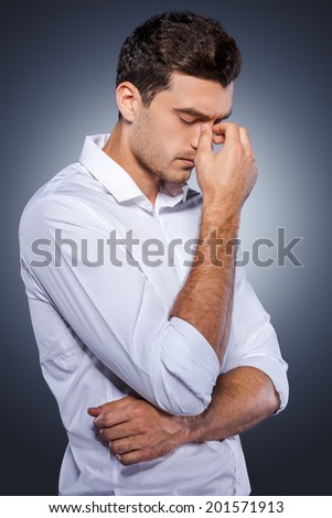 Lost in thoughts. Side view of handsome young man in white shirt holding hand in hair and looking away while standing against grey background - stock photo