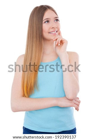 Lost in thoughts. Thoughtful teenage girl holding hand on chin and looking away while standing isolated on white - stock photo