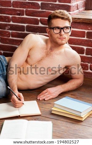Lost in thoughts. Thoughtful young  shirtless man writing something in note pad and looking away while lying on the floor at his apartment - stock photo