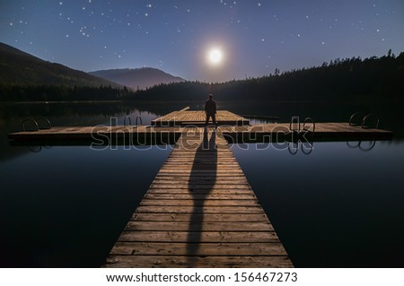 Lost lake in Whistler man looking at moon - stock photo