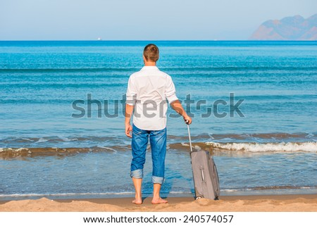 lost on a desert island man looks at the leaving ships - stock photo