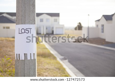 lost sign on a lampost in a suburban street - stock photo