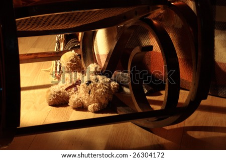 Lost teddy bear under rocking chair - stock photo