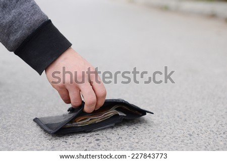 Lost wallet. Low section of man picking up fallen wallet on street.Lost black leather wallet with money lost at street - stock photo