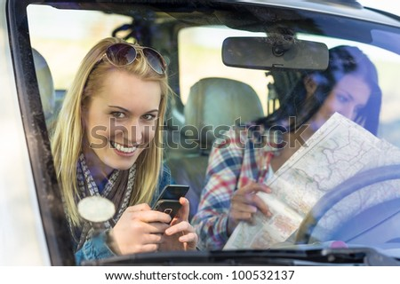 Lost with map two young friends in car enjoy road trip - stock photo