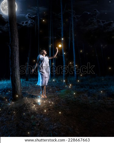 Lost young woman at night forest with full moon jumping high to reach firefly - stock photo