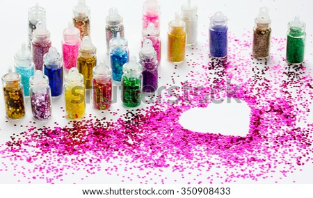 Lot colored glitters make-up in a small bottle on a white background. - stock photo