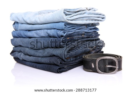 lot of blue jeans with belt isolated on white - stock photo