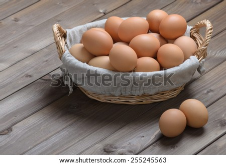 lot of chicken eggs in a basket on a wooden table - stock photo