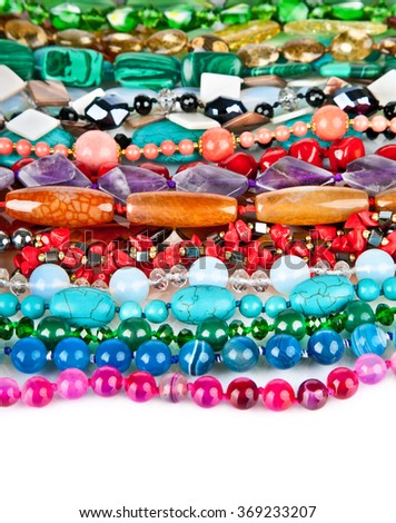 Lot of colored beads from different minerals and stone background - stock photo