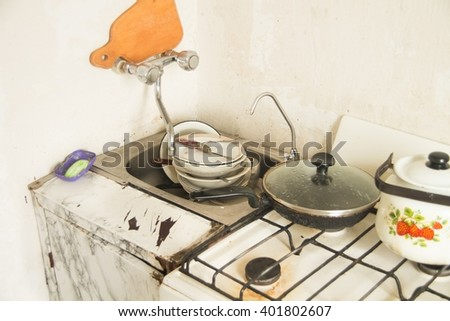 Lot of dirty dishes in the old kitchen - stock photo