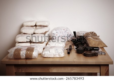Lot of drugs seized by police on table with weapons - stock photo