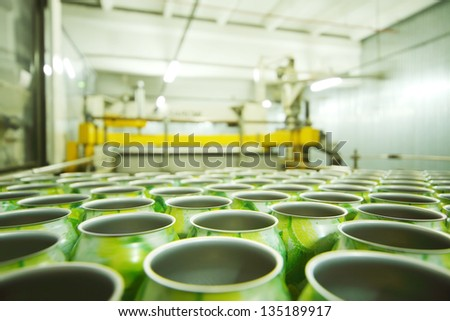 Lot of empty aluminum cans for drinks in light manufactory at large factory. - stock photo