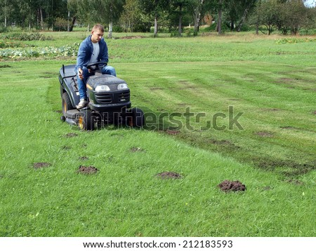 Lot of molehills disturb mowing the grass - stock photo