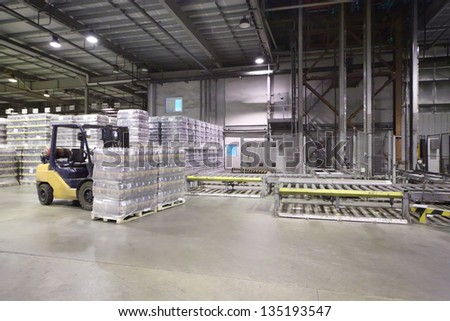 Lot of packaged beer bottles in large warehouse and loader machine. - stock photo